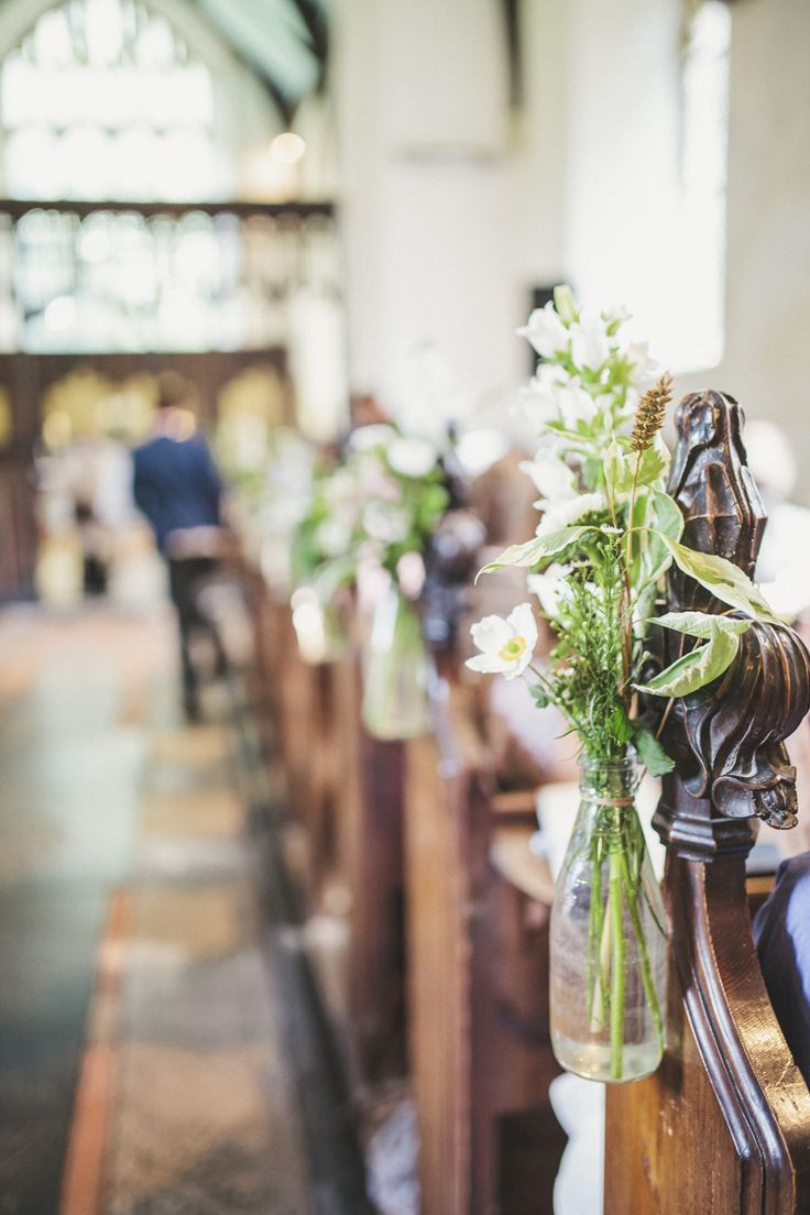 Glass bottles filled with wild flower stems on the end of the church pews -   Image by Matt Ethan Photography - Bride wears a Sincerity Bridal gown at a rustic outdoor wedding in Norfolk with nautical colour scheme.