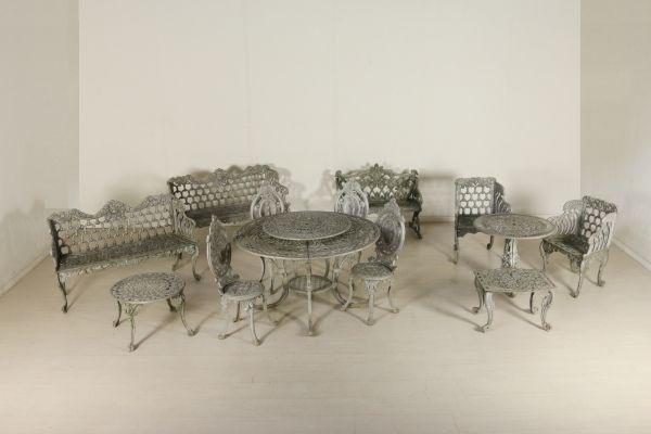 Dalla linea mossa, traforato e lavorato in alluminio a imitare ghisa. Composto da tavolo con vassoio (77x120), panchina (78x94x47), coppia panchine (81x133x46), tavolino tondo salotto (39x59), tavolino sagomato (38x58x50), tavolino tondo (61x72), quattro sedie (96x38x43), due poltrone (79x59x45).