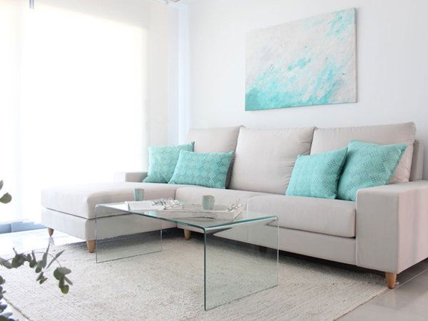 Salón con sofá en claro, cojines azules y mesa de centro en cristal