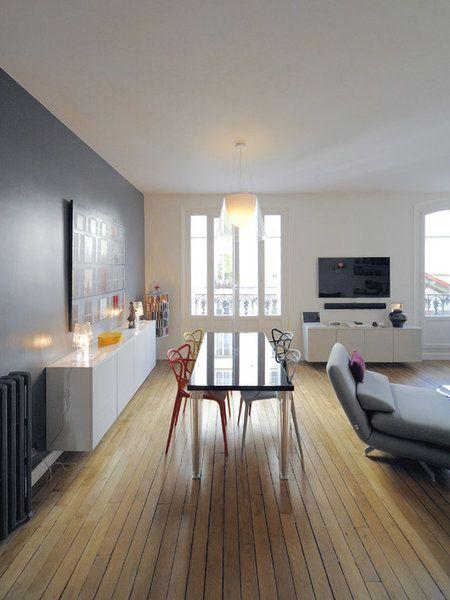 Dans la pièce à vivre, un mur peint en gris anthracite, côté salle à manger, met en valeur une enfilade laquée blanc. Un coin repas intégré avec une grande table de salle à manger et des chaises design (Kartell).Le radiateur en fonte apporte une touche rétro.