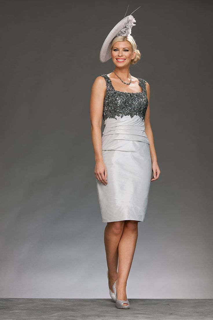 The knee length fitted dress has a square neck and straps, with the bust and straps overlaid with contrasting lace. From under the bust there is ruching to emphasis the waist and give a flattering silhouette. The bolero jacket has matching lace around the cuffs. Product Code: 337 Colour: Cool Grey