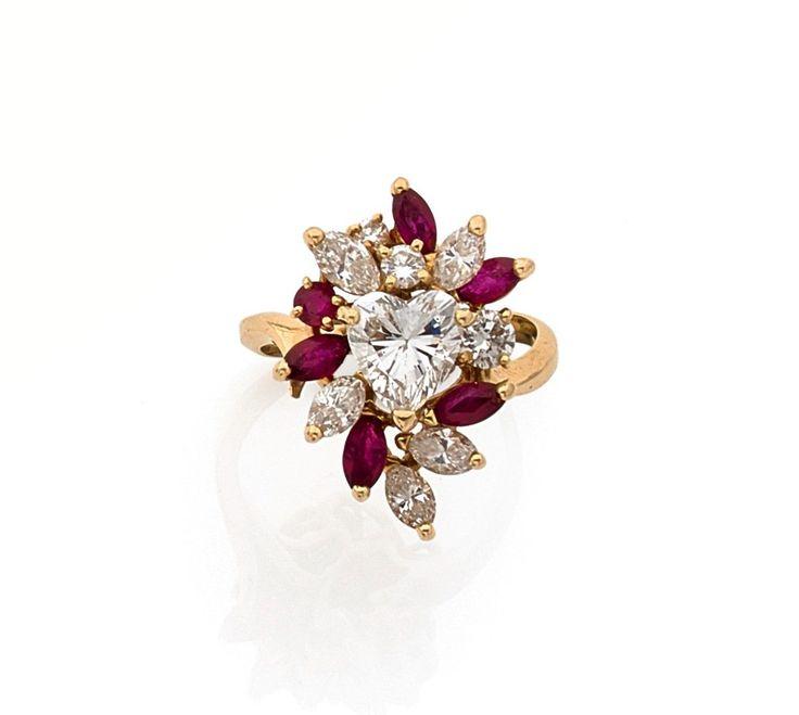 BAGUE en or jaune 18k (750), ornée d'un diamant taillé en coeur dans un semi de rubis et de diamants taillés en brillant ou en navette Poids du diamant: env. 1.15 ct Poids brut: 6.43 g  Estimation 2.500/3.500€