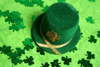 The color green is associated with Saint Patrick's day. Known symbols are shamrocks and green clothing, like a green hat.