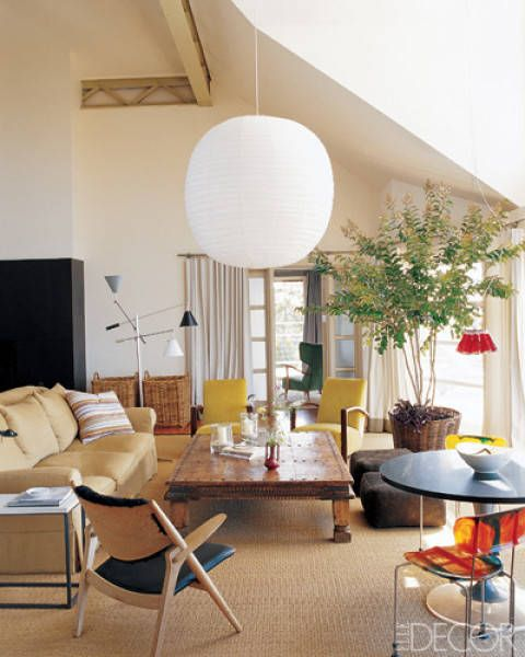 In a Hamptons home designed by Joe D'Urso and Tom Flynn, a Noguchi Akari light sculpture gives the living room a focal point. The vintage Triennale floor lamp is by Arteluce, and the French Deco armchairs are upholstered in a Christopher Hyland cotton velvet. In the foreground, the Campari light fixture is from Ingo Maurer, and the Broadway resin side chairs are by Gaetano Pesce from DDC.    - ELLEDecor.com