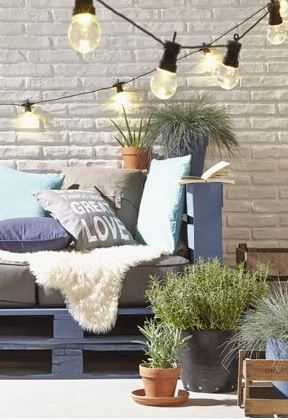 This creative use of palettes makes for some beautiful outdoor furniture. We love the atmospheric lighting and those gorgeous painted white brick walls.