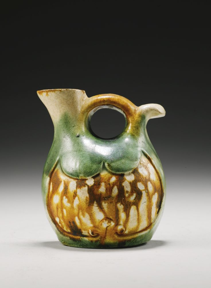 A Sancai-Glazed Flat-Backed Ewer Tang Dynasty modelled in the form of a Persian leather water bottle, the flat-backed globular body with flaring spout and high arched handle, the front face with an intaglio ochre and cream-splashed shield-shaped panel, all reserved on a green-glazed ground 12.5cm., 5in.