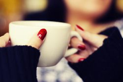 Red nails, black sweater, white cup