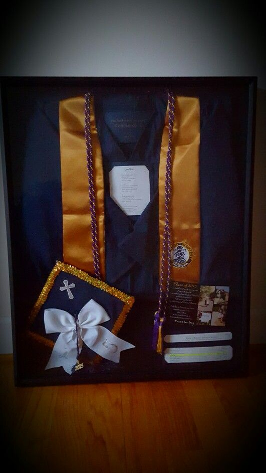 College graduation shadow box featuring cap, gown, cords, alma mater, graduation announcement, and name in the program