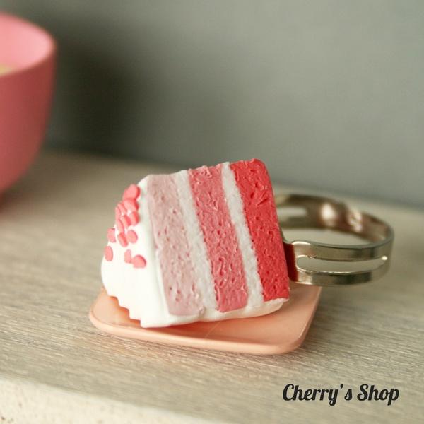 Ajoutez une touche de gourmandise à votre tenue avec cette bague en forme de part de gâteau. *Ceci n'est pas un jouet, il ne doit pas être laissé