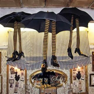 Create a whimsical atmosphere in your shop with this adorable store display idea using old umbrellas, striped stockings with tissue and thrift store shoes from CURIOUS SOFA. #halloween #storedisplay