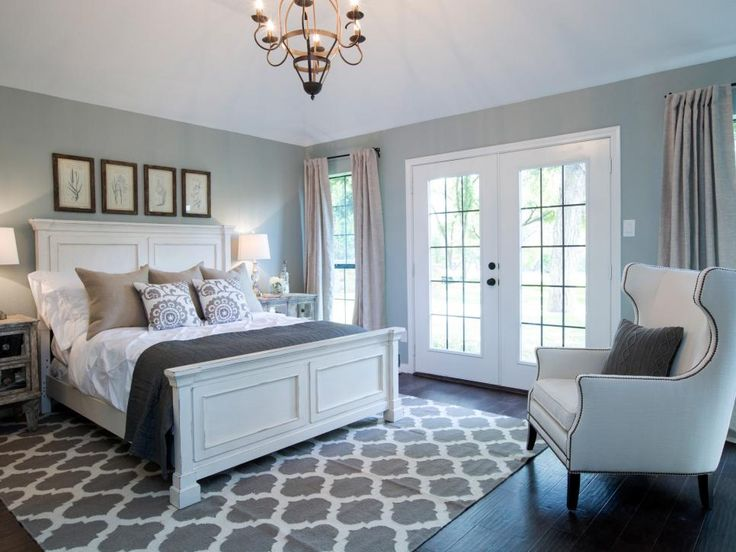 The newly redesigned master bedroom has dark wood floors, large windows and French doors, linen drapes and blue-gray walls.
