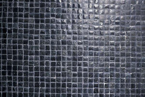 Je zou kleine, donkere steentjes kunnen gebruiken om patronen van grote tegels op te breken.