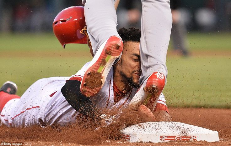 Billy Hamilton  of the Cincinnati Reds slides into the legs of Jhonny Peralta of the St Louis Cardinals during a MLB match