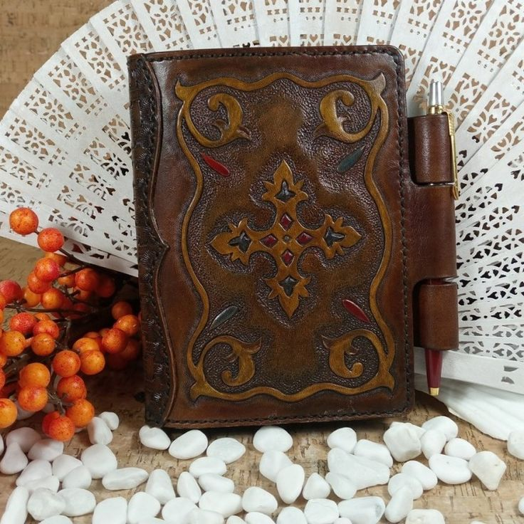 Leather notebook cover ancient ornament (No Shipping Costs - Made to Order) Holds an A6 notebook and has three loops that hold your pen and act as a closure. The notebook cover is dyed brown and has a hand carved ancient ornament inside a frame of scrolls. Some of the details are subtly coloured in blue and red. The spine is decorated with a tooled basket weave. The inside of the cover is lined with soft pig skin #b2zoneservice #b2zonemagazine