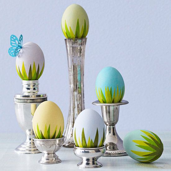 Easter eggs, decorated with paper grass blades, in silver candlestick holders