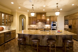 Large, open kitchen with large island, wood corbels, glass upper cabinet doors, subzero refrigerator with built in wood appliance panels.