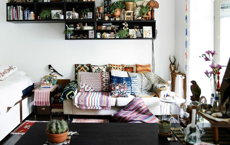 Sitting room with sofa piled with cushion and textiles. Shelving with eclectic mix of books and mementos