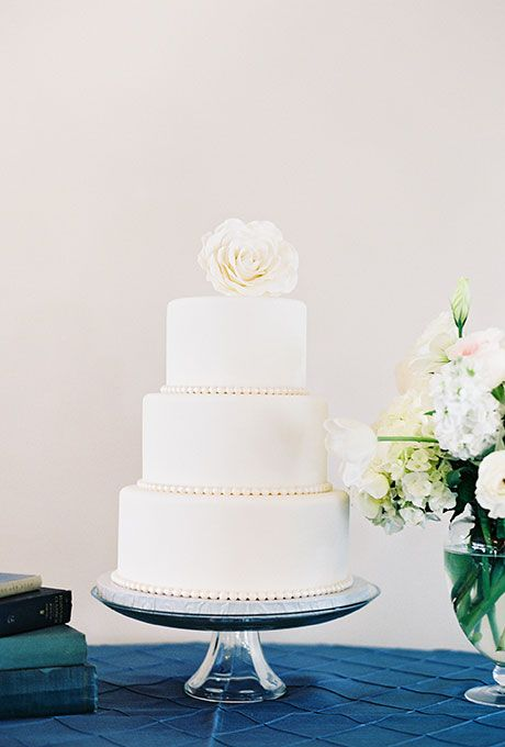 A three-tier white wedding cake with pearl accents and a fresh flower | Brides.com