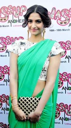 Sonam Kapoor shows how to team up a plain saree with a kitsch blouse.