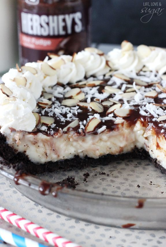 Almond Joy Pie - a custard-like pie full of coconut flavor, topped with chocolate sauce, coconut, almonds and whipped cream