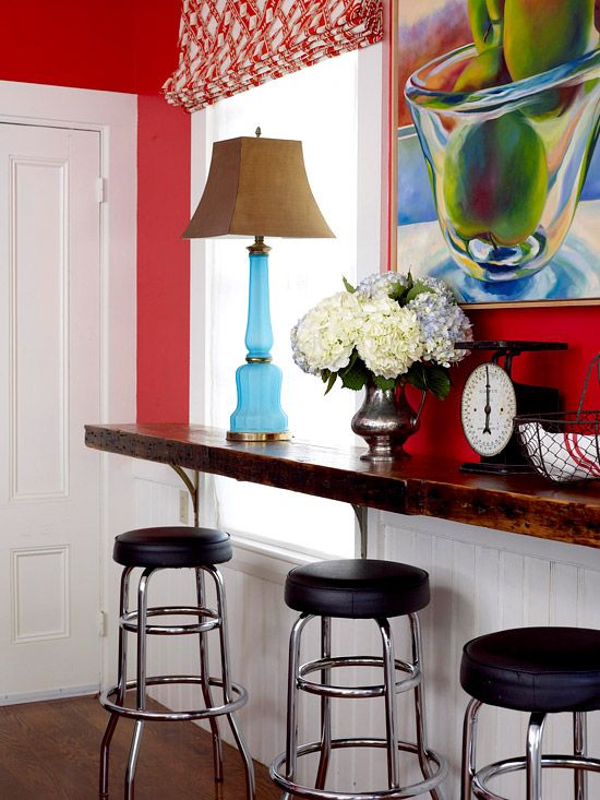 To create additional seating, an eating counter was installed beneath the kitchen's two windows, using floor joists held up by antique brackets found in the home's basement. Retro barstools enhance the room's fun, easygoing style./