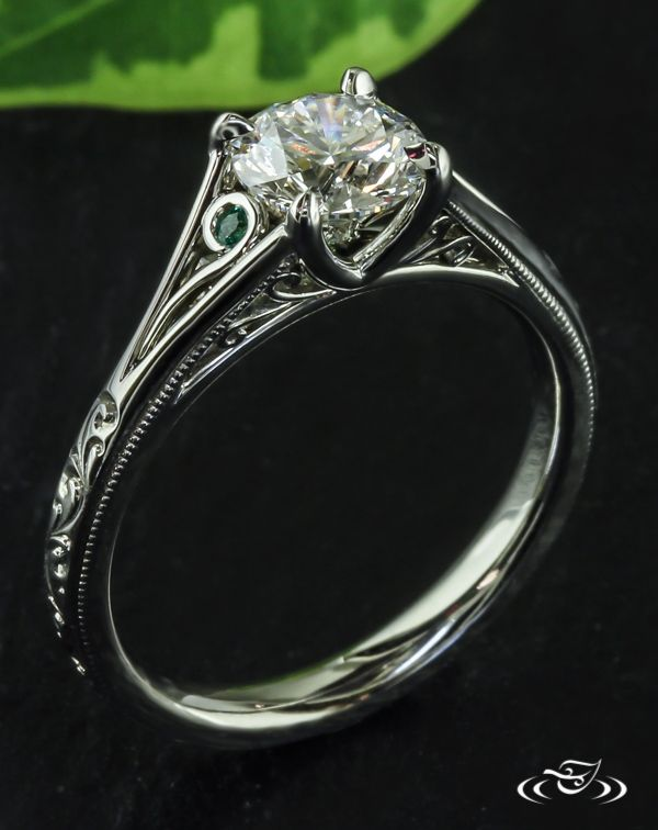 Emerald Twist Engagement RingThis platinum antique style chevron prong set diamond engagement ring features emeralds caught in a twist of filagree. #Ido #GreenLakeMade #EngagementRing