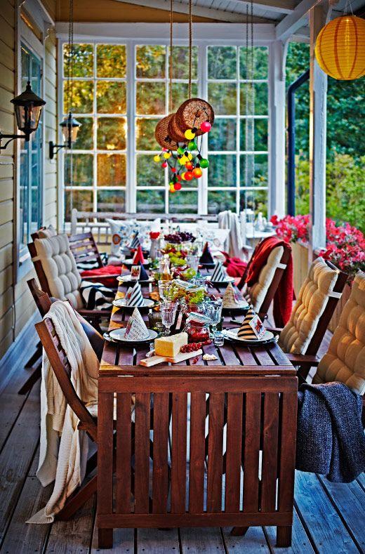 Zastawiony stół na werandzie z krzesłami i łańcuchami oświetleniowymi zasilanymi energią słoneczną w jasnych kolorach