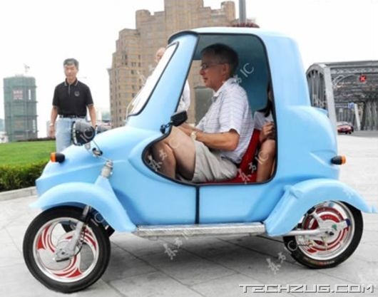 "Worlds Cheapest Electric Car: ""Why no... I'm not the least bit cramped. What makes you say that? Nothing could be further...How did you know?"""