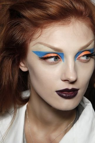 Dior Orange and Blue blunt geometric shadow, deep wine lips - super high arched brow. tip: cover outer 1/2 of natural brow (or entire brow) via gluestick method or spirit gum + brow wax. Draw in new brow using short quick strokes.