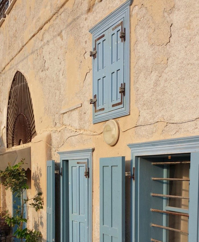 Pale blue wood shutters on a rustic style home in Akko next to the Mediterranean Sea