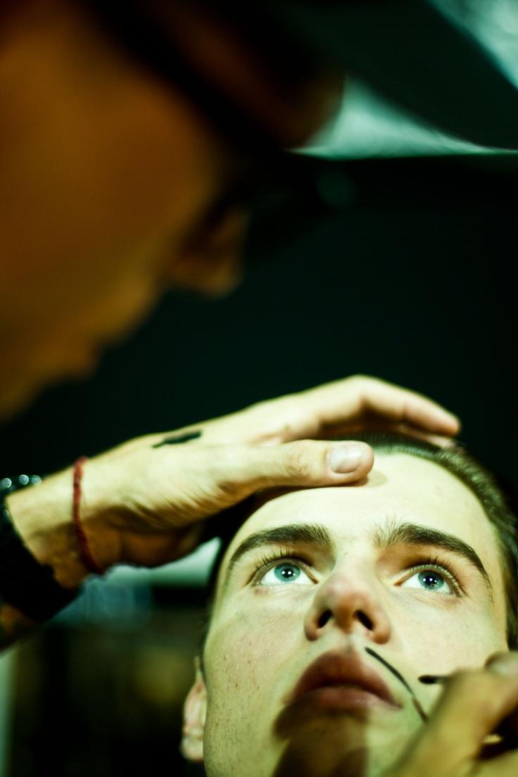 Un modelo es maquillado para la presentación de la colección Otoño Invierno de Joao Pimenta, durante la Semana de la Moda de Sao Paulo.. La propuesta remite a los años 30, cuando los hombres andaban con el pelo engominado. El bigote es una forma humorística de mostrar al hombre típico de la época. Xinhua
