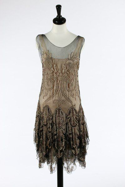 A Callot Soeurs couture black tulle and pearl beaded flapper dress, 1927. The matching rose-pink satin slip with printed gold on ivory silk label 'Callot Soeurs, Paris, Hiver, 1927-28, Nouvelle Marque Déposée' and numbered in ink '2741', the transparent tulle adorned with pink metal and pearl beaded arabesques with gold stem-stitch tendrils, the skirt falling in elaborate beaded petal-like tiers