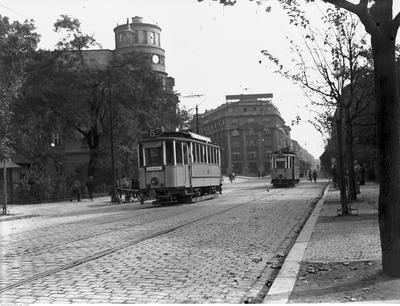 Opis obrazu: Tramwaje typu SN1 linii 6 u wylotu ul. Siennej. W głębi widoczny Pałac Prasy i gmach Poczty Głównej. Data wydarzenia: 1936-09