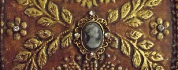 Baú em MDF, com tampa abaulada e saia, totalmente revestido com papel texturizado, complementado com aljofres, camafeus, medalhões, strass e envelhecimento. Interior flocado na cor bordô.
