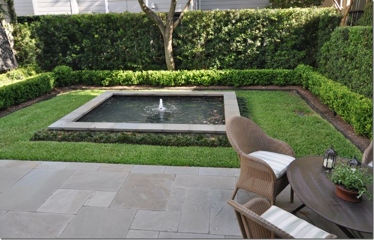 Fountain surrounded by grass and boxwood.  A pleasant small garden that appears to be low maintenance too.