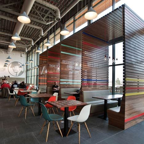 ③気軽に打合せできるスペース Nike Office (Netherlands) Design Studio: UXUS Dining area with slatted booths adorned with painted logos