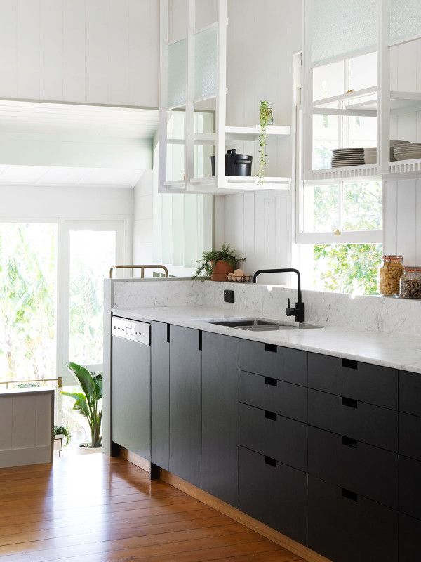 Kitchen: matt black cabinetry with cut-out handles, white open shelving, white marble benchtop and short splashback, black tapware, window over sink, timber floorboards, natural light,