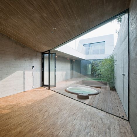A courtyard garden divides the two sides of this concrete house in Vienna, which…