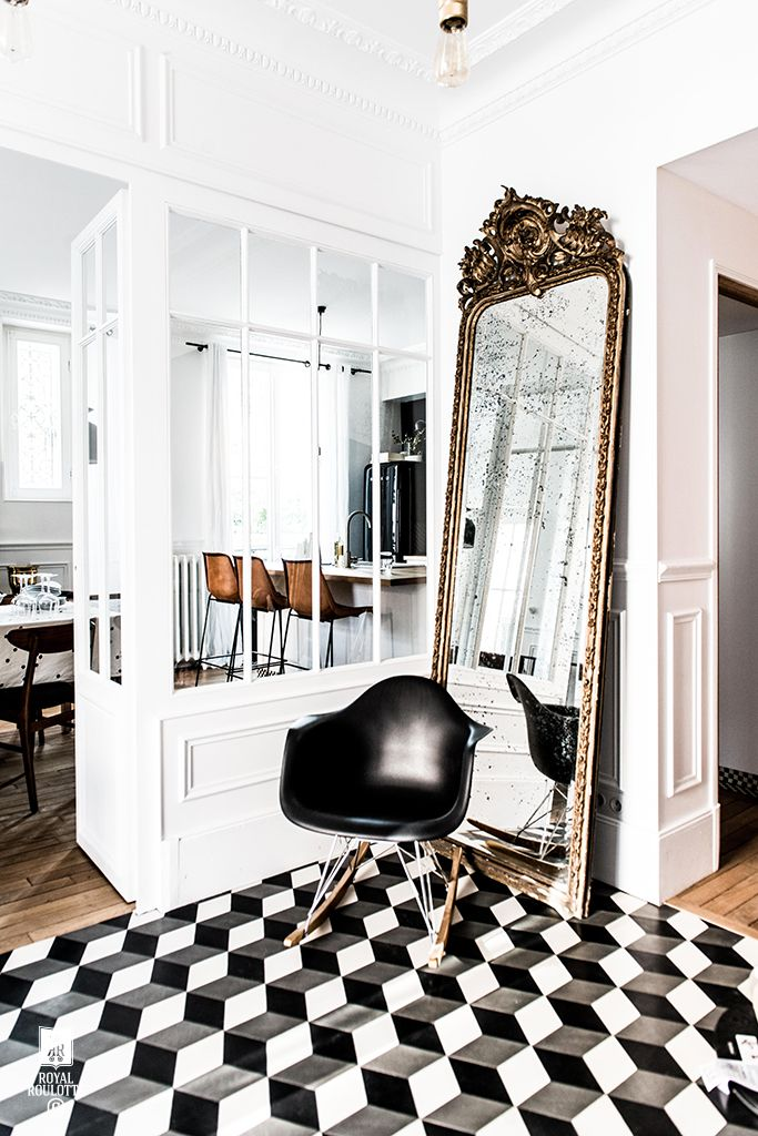 An antique mirror leaning on foyer with a modern black chair and gorgeous tiled floors: