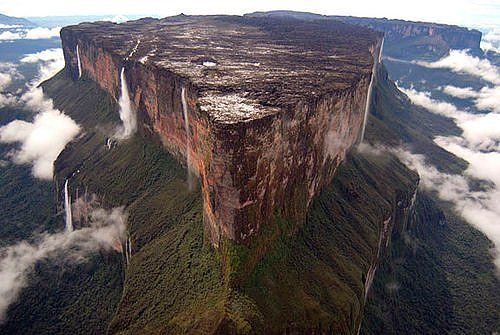 Mount Roraima is a massive tabletop mountain that is found in Venezuela/Brazil/ Guyana. The side facing Brazil and the side facing Guyana are both vertical cliffs that reach 400 meters in height, whereas the side facing Venezuela is a steep incline and although steep it is accessible. This unique mountain boats a variety of plant life, much of it unique and also creates some of the largest and most spectacular waterfalls in the world.