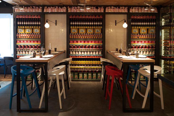 mesas altas de madera con patas metalicas taburetes de colores estanterias y luces de pared negras