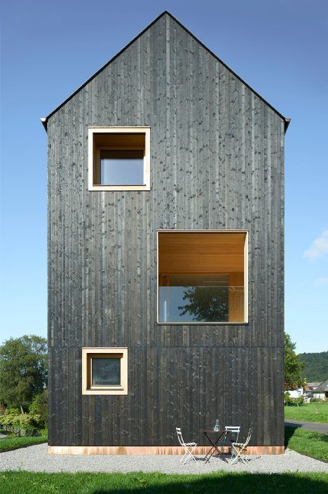 This tall, gabled house by Bernardo Bader Architekten is covered in lengths of blackened timber