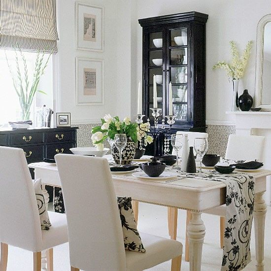 Black and white in a dining room looks very elegant. Here, a dining table from Homes in Heaven dressed with a monochrome runner and white china makes a smart statement. A black cabinet and chest of drawers provide sleek storage, while a slightly textured cream carpet from Kersaint Cobb and a two-tone fabric blind from Malabar complete the dramatic look.