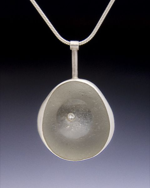 Contemporary Jewelry Design by Andrea Williams: Sea Glass & Diamond Pendant: This is an ealry work, before I stopped using diamons all together. A mother and her only daughter found this unusual concave sea glass while walking the beach together. As a gift to her mother, the daughter had it set with a singular stone in this Sterling pendant to symbolize their unique friendship and how valued her time with her mother is.