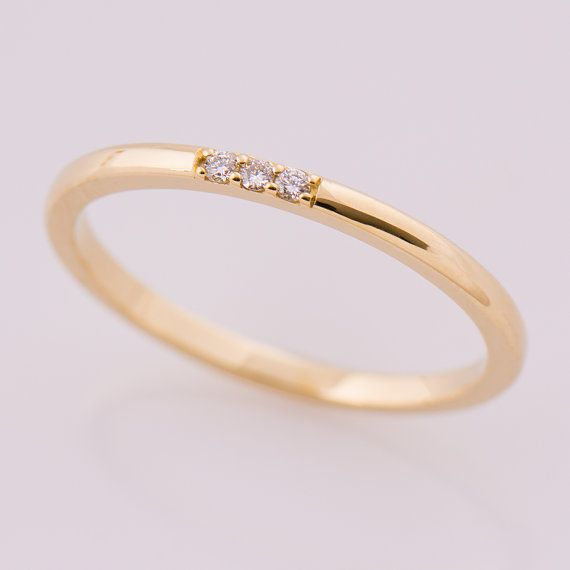 Dainty, stackable single diamond ring in 14K yellow gold, set with a clear diamond.  The ring surface is elegant and rounded shape while the sides are