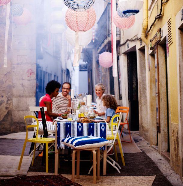 Ein fertig gedeckter Tisch im Freien, gestaltet u. a. mit REIDAR Stühlen für drinnen und draußen in Gelb, SOLVINDEN LED-Solarhängeleuchte in Kugelform in Rot/Weiß und Blau/Weiß