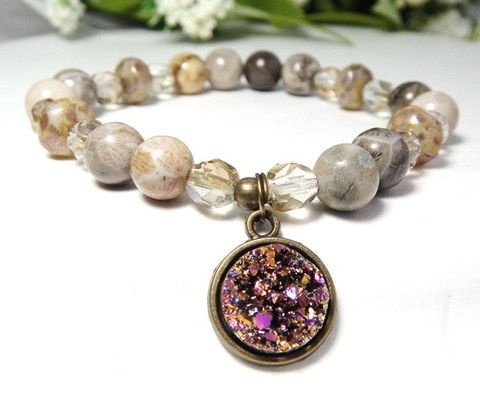 Unique charm bracelet features a man-made Druzy Charm that is golden color with bursts of fuchsia in the light. It is surrounded by 8mm Fossil stone and Czech glass beads. Fossil Stone Properties: A s