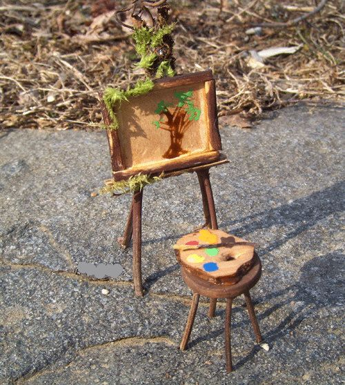 Dollhouse Miniature ~~ ARTIST EASEL ~~ STOOL and PALETTE Woodland Faery Easel Handcrafted with Twig Branches Moss and Grapevine Tendrils Complete with Attached Framed Painting, Wooden Stool, Paint Palette and Brush Easel Measures 4 1/2 Inches Tall Stool Measures 1 1/2 Tall -------------------------------------------------- Adorable Displayed in a Plant Pot Miniature Garden or Dollhouse -------------------------------------------- FOR INDOOR USE ONLY NOT WEATHER PROOF