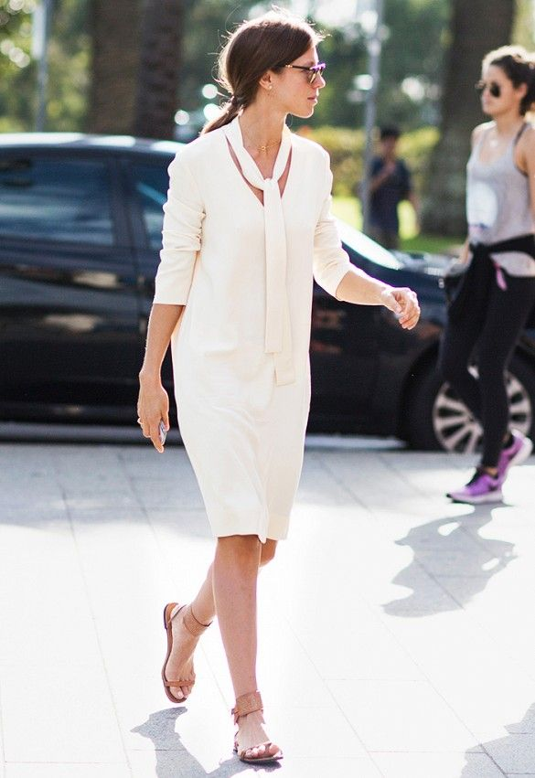 A cream-colored sweater dress is worn with a matching scarf, gold jewelry, and flat sandals