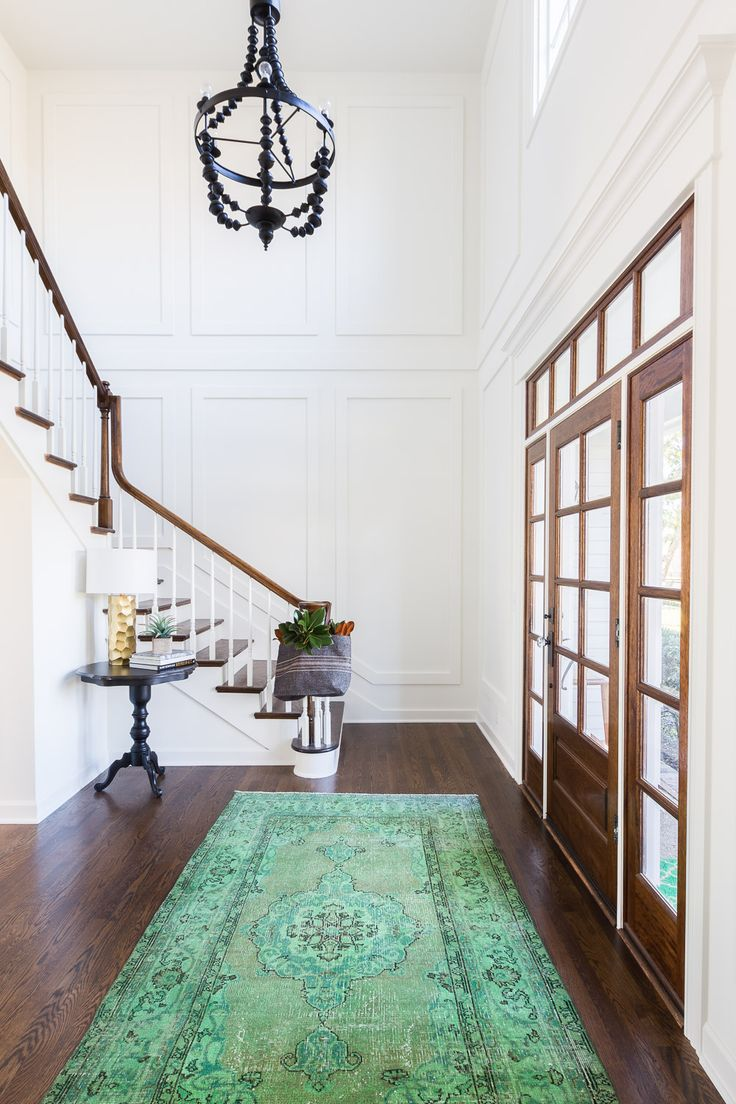 Entryway with wooden paneled window door and statement green rug | Redo Home + Design